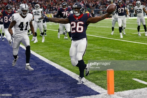 HOUSTON, TX - JANUARY 07: Lamar Miller #26 of the Houston Texans rushes for a touchdown during the first quarter against the Oakland Raiders in their AFC Wild Card game at NRG Stadium on January 7, 2017 in Houston, Texas. (Photo by Bob Levey/Getty Images)